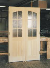 double inner arch interior door unit pattern obscured glass on top and wood panels at the bottom renovation project in long island ny