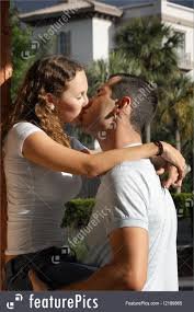 people cute young couple kissing outside in tropical setting
