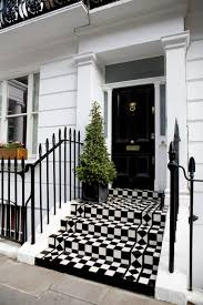 standing over a vibrant checker patterned set of steps this black door features a plethora