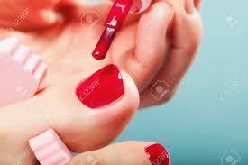 ペディキュア適用ピンクつま先セパレーター青い背景の赤い爪を持つ女性の足の足します