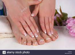 Girl hands and bare feet with french manicure and pedicure nails polish on  white towel in beauty salon and decorative pink flowers in background Stock  Photo - Alamy