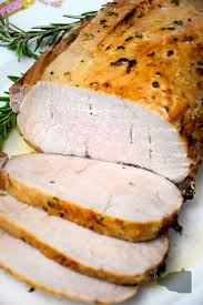 air fryer maple glazed pork loin on serving platter with 3 slices cut and lying in