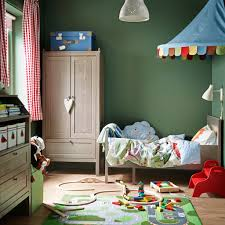 A blue children's bedroom with white extendable bed, wardrobe, table and  desk.