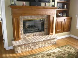 interior brown wooden fireplace mantel with cream stone surround and cream hearth connected by brown