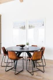 fabulous dining clean white walls with y leather chairs flanking a round mid century modern style table