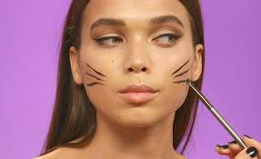 model drawing whiskers with eyeliner to create a cute cat makeup look