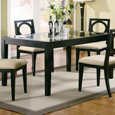 rectangle glass top table with black wooden frame also four legs plus chairs cream seat dining