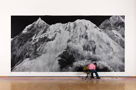 photograph of artist working on large scale chalk drawing of mountain on gallery wall