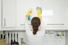 rear view at an attractive young woman cleaning a surface of white kitchen wall cabinet