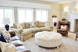 chic living room design with leather wingback chair and round ottoman coffee table also sisal carpet