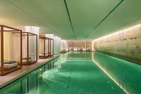 indoor pool. Indoor Pool Illuminated Water And Lounge Chairs Outside Of I