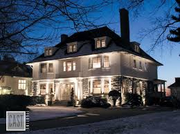 lovely landscape lighting using cast lighting fixtures to showcase this gorgeous white colonial in freshly fallen