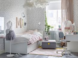 Children's bedroom with white walls with black spots and a white bed with  pale pink bedding