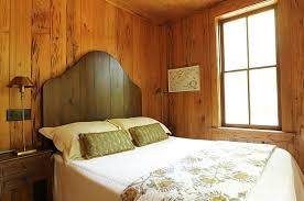 ... Simple wooden headboard adds to the beauty of the rustic, elegant  bedroom [Design:
