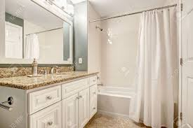 stock photo white bathroom vanity cabinet with granite top and mirror aqua color walls and beige tile floor