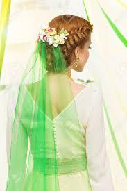 編みこみの髪型花髪で緑のベールとドレスの美しい若い女性の背面し