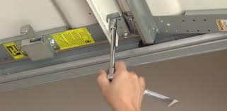 using socket wrench to tighten a loose bolt on garage door