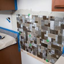 tile backsplash held into place with thinset on the wall