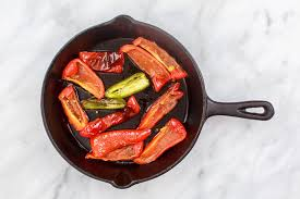 red peppers being roasted in a skillet