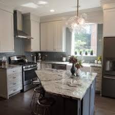Modern Bubble Chandelier Over Diamond Cut, Marble Countertop Island And Vertical  Subway Tile Kitchen Backsplash