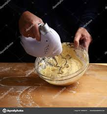 female hands stirring dough with a mixer for cake or bread in a bowl on a wooden kitchen worktop preparation for baking dark background with copy space
