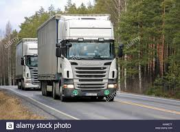 salo finland march 17 2017 two white scania r420 curtainsider semi trailer trucks from poland move along rural road in south of finland