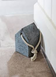 A house-shaped door stop in heavy granite