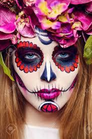 closeup portrait of calavera catrina young woman with sugar skull makeup dia de los