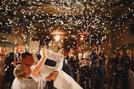 Bride And Groom Kiss Under A Confetti Cannon Shower At Their