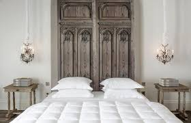 french bedroom features ornate carved wood doors used as a headboard on queen bed dressed in white bedding flanked by crystal chandeliers hanging over