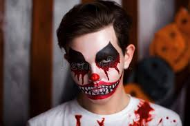 young guy with creative body painting horror clown boy is a carnival character with colorful makeup blood on face and shoulders