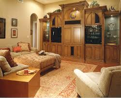 custom wall unit in walnut and etched glass panels graces a large family room with rust