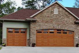 one double and one single fiberglass garage door on the front of a stone facade are