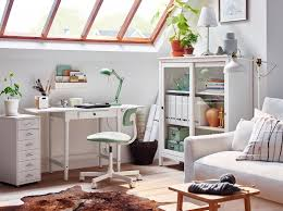 A traditional INGATORP desk in white in a sitting room with glass sloped  ceiling.
