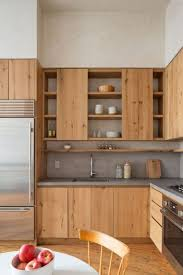 a light colored wooden kitchen is made more modern with concrete countertops and a backsplash