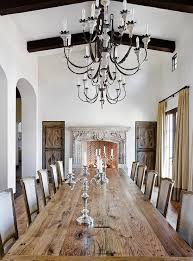 french dining room features a long plank dining table lined with french linen dining chairs illuminated by french candle chandeliers placed in front of a