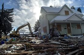 file a bulldozer operator steps toward the cab to continue cleanup of this nuisance home