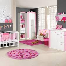 large baby room with modern design on the white iron crib and storage with round pink rug