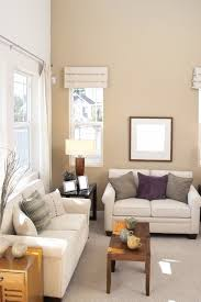 a living room in light taupe and ivory with side tables in varying shades of wood beautiful small livingroom