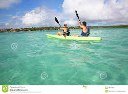Transparent Canoe Kayak Couple Rowing In Canoe In A Crystal Clear Water In Tropics Stock