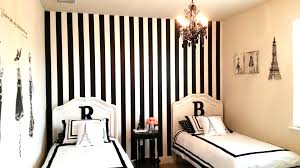 double beds with paris themed bedding before the white and black stripped wall plus black chandelier