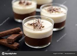 no bake layered chocolate mousse and cheesecake with chocolate covered wafer cookie crumbs topping in clear glass dessert bowls on dark background
