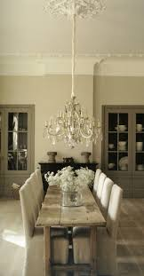 mixing plank table antique chandelier slip chairs pared back elegance