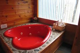 red heart shaped jacuzzi tub in private room at just us a 1 bedroom cabin