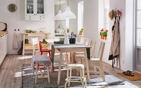 a light dining room with white stained dining table and chairs with e for 9 people