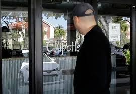 a customer stands outside as he looks into a closed chipotle restaurant on his lunch break