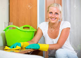dusting furniture. Smiling Young Woman In Rubber Gloves Dusting Furniture At Home Stock Photo - 84437637
