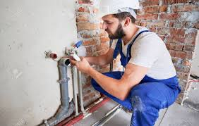 Young Plumber, Wearing Blue Uniform And White Helmet Working.. Stock Photo, Picture And Royalty Free Image. Image 159932995.