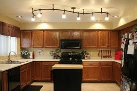 kitchen ceiling spot lighting above small island table with maple wood butcher block toward slide in ceiling spot lighting