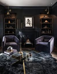purple velvet chairs triangluar glass top coffee table books open shelving cabinets fireplace candle holder textured rug wooden floor candles